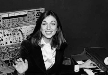 Woman sitting at keyboard in front of synthesizer